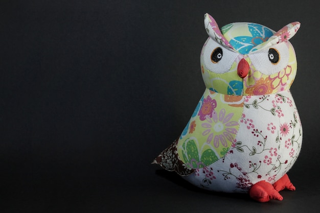 Owl toy on black. wise owl in the night with place for text