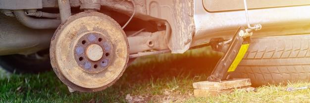 Own repair of car drum brake himself. repair of broken car drum brake disassembled outdoor. banner. flare