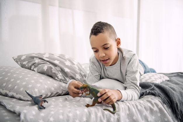 Own world. musing positive afro american boy lying on bed while playing with dinosaurs toys