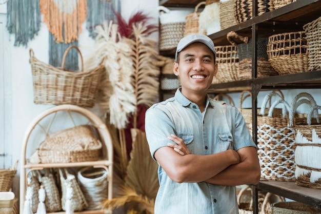 Владелец ремесленного бизнеса со скрещенными руками в мастерской с поделками ручной работы на полке