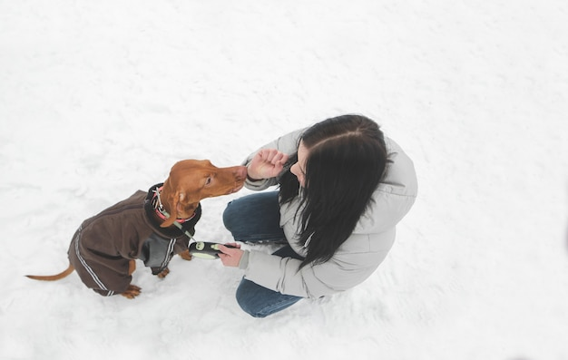 Хозяин и милая коричневая собачка в одежде сидят на снегу и играют.