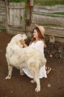 Собака-владелец и лабрадор ретривер во дворе. женщина в белом платье. золотистый ретривер.