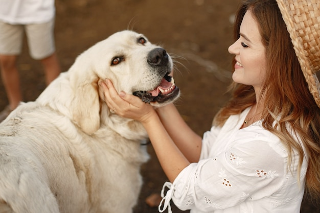 마당에 소유자와 래브라도 리트리버 강아지. 흰 드레스에 여자입니다. 골든 리트리버.