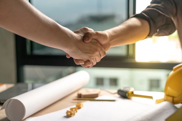 Owner and constructor  is agree and shake hands to celebrate in success of finish in contract home building construction project