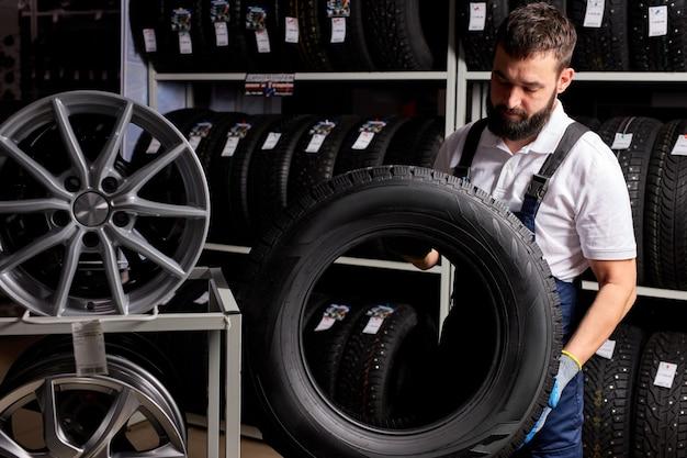 スーパーマーケットのモールで最高のタイヤを持ち、ゴム製の車のホイールを測定しているオーナーのガレージショップ。職場で