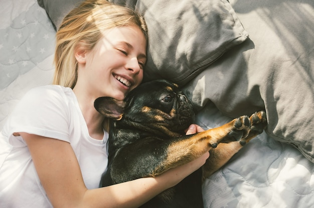 Owner hugs her dog of breed french bulldog on bed