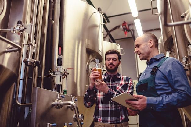醸造所で労働者とビールを検査する所有者