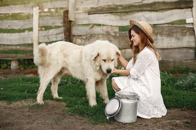 Proprietario e cane labrador retriever in un cortile. donna in abito bianco. golden retriever.