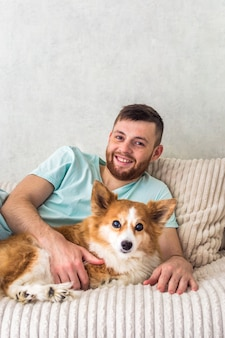 Owner lies on the bed with his ginger dog hugging.