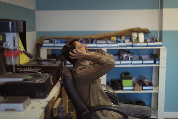 目を閉じて自転車のワークショップで音楽を聴いている所有者