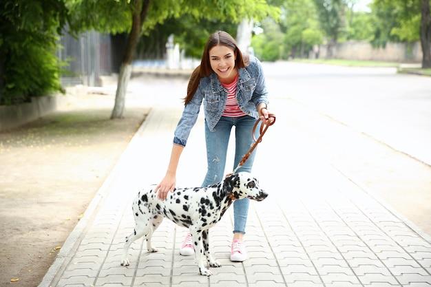 Владелец с далматинской собакой гуляет на свежем воздухе