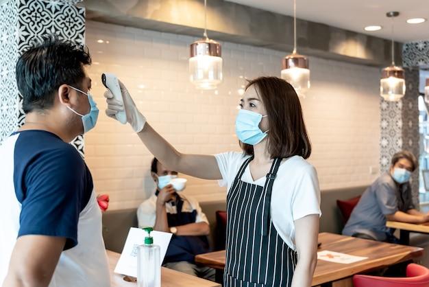 마스크를 쓴 소유자 여성 고객 서비스, 체온계를 사용하여 발열 측정