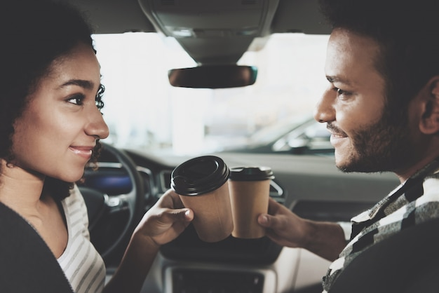 Owners of luxurious car drink coffee purchasing.