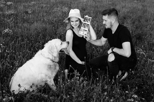 소유자는 자신의 개, 흰색 래브라도에게 초음파 사진을 보여줍니다. 흑백 사진. 아이를 기다리고 있습니다. 임신 관리. 현대적인 검사 방법. 임신의 행복한 순간.