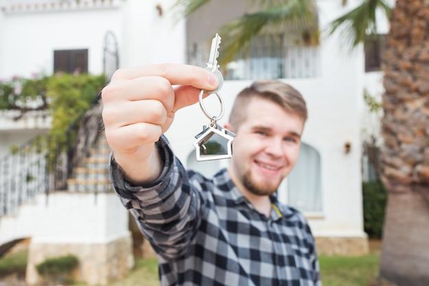 Собственность, недвижимость, собственность и концепция арендатора - портрет веселого молодого человека, держащего ключ от нового дома