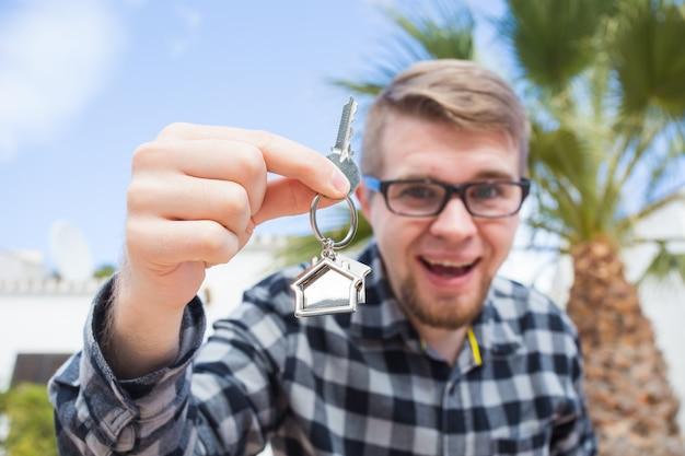 Собственность, недвижимость, собственность и концепция арендатора - портрет веселого молодого человека, держащего ключ