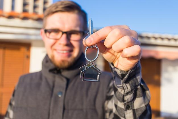 Собственность недвижимого имущества и портрет концепции арендатора веселого молодого человека, держащего ключ