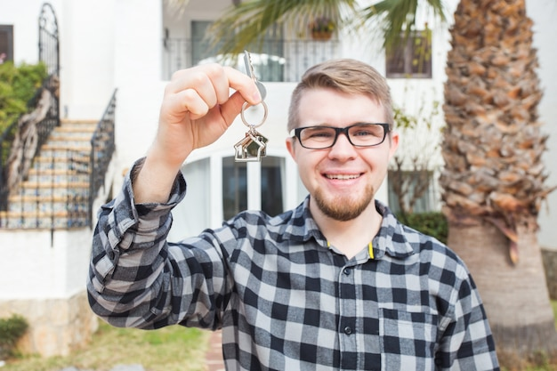 Ownership, real estate, property and tenant concept - portrait of a cheerful young man holding key from new home.