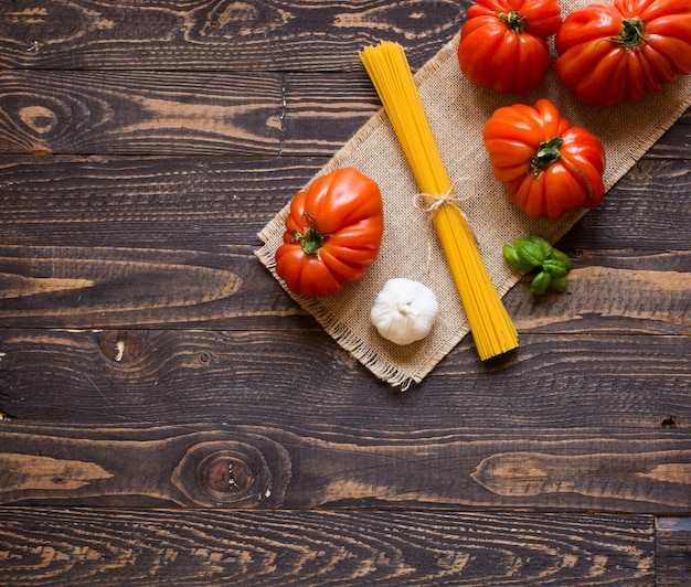 Ox heart tomatoes on rustic wood background free space for text.
