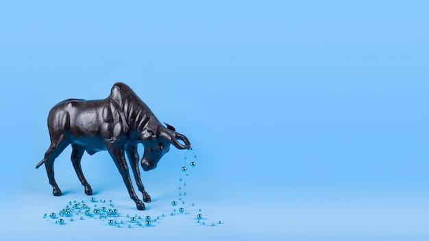 Бык с елочным шаром на рогах на синем фоне