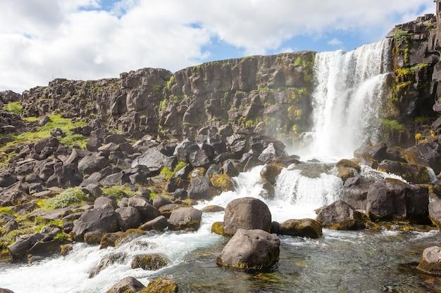 Взгляд летнего дня водопада оксарарфосс, тингвеллир, исландия. исландский водопад
