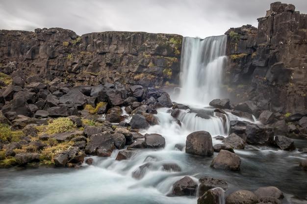 Cascata oxararfoss a thingvellir, islanda sotto un cielo velato