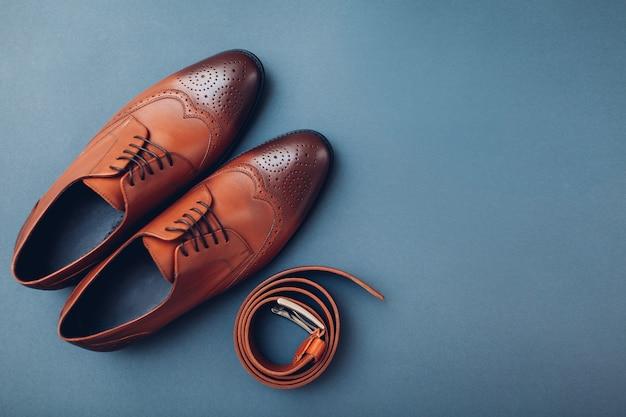 Оксфордские мужские ботинки с аксессуарами. мужская мода. классическая коричневая кожаная обувь с поясом. космос