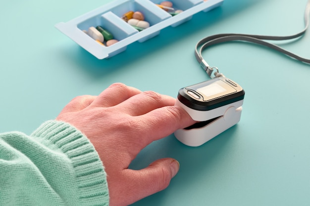 Oximeter, digital device to measure person's oxygen saturation on caucasian female hand. reduced oxygenation - emergency sign of pneumonia caused by bacteria of viruses including coronavirus.