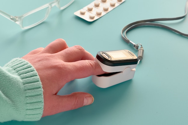 Oximeter, finger digital device to measure person's oxygen saturation. reduced oxygenation is emergency sign of pneumonia caused by bacteria, flu or corona virus. device on caucasian female hand.