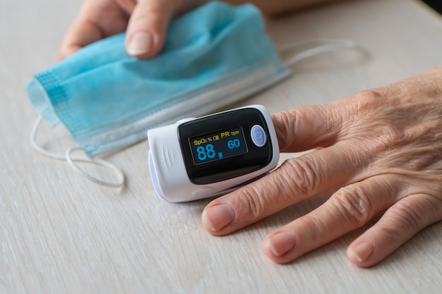 Oximeter test elder patient in prevention of covid 19 pneumonia, examining senior woman using oximeter at home. the woman herself measures the blood saturation.