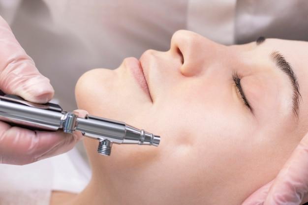 Кислородная мезотерапия. aquapilling. процедура косметического пилинга. безинъекционная мезотерапия для молодой девушки в салоне красоты.