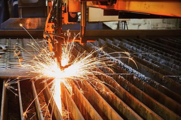 Кислородная горелка режет стальной лист. газорезательный станок с чпу. яркий сноп искр расплавленного металла