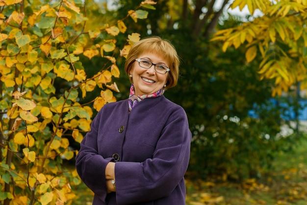 가을 시즌에 공원에서 안경에 성숙한 여자의 oyful 초상화 긍정적 인 낙관적 표정으로 웃는 중년 아가씨 노란 잎의 아름다운 배경