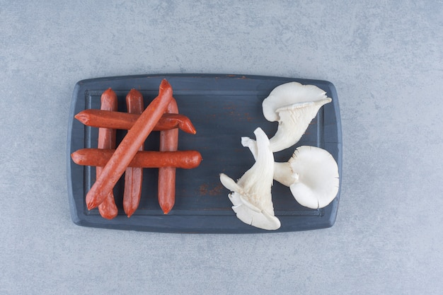 Oyster mushroom and salami on black board.