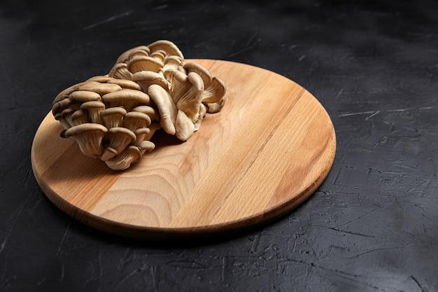 Вешенки, деревянная разделочная доска на черном фоне. группа сырых съедобных грибов на темном каменном столе, пищевой ингредиент