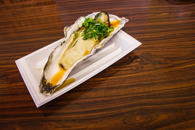 The oyster seasoning with garnish japanese style at put on the table in kuromon ichiba mar