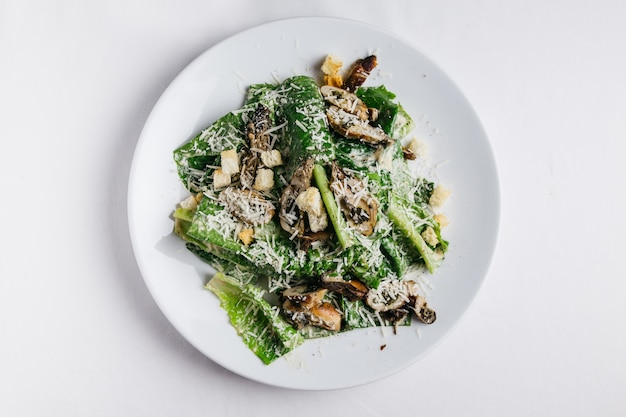 Oysters caesar salad served in white plate over white tablecloth