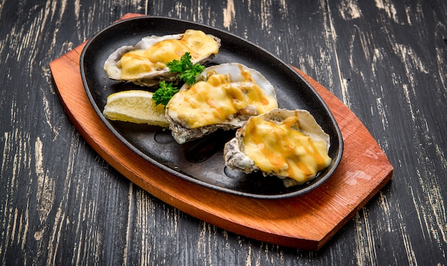 Oysters in a pan in a creamy sauce and cheese
