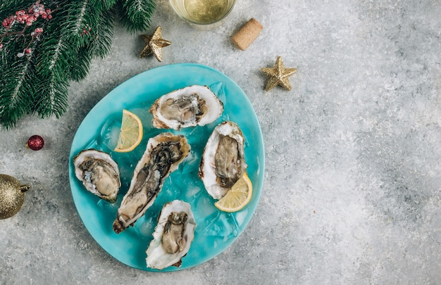 Oysters with lemon, ice and white wine on concrete background with a festive decor. christmas dinner