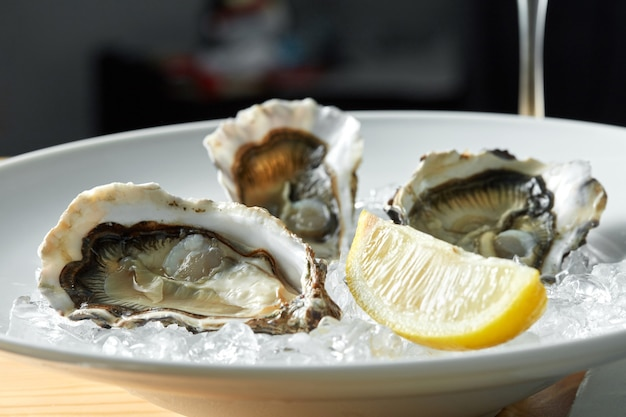 Oysters with lemon on plates on a table with a glass of white wine