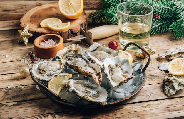Oysters with lemon on a vintage dish on a rustic wooden background with a festive decor.