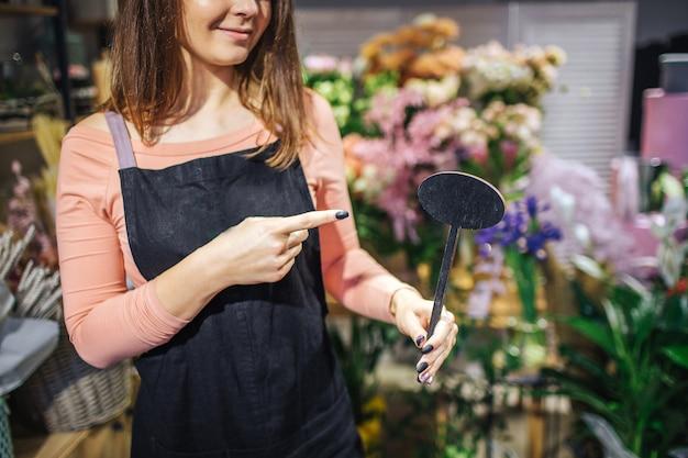Отрежьте взгляд точки флориста oyung женской на черной деревянной вещи в руке. она стоит перед цветами и растениями. молодая женщина носить черный фартук.