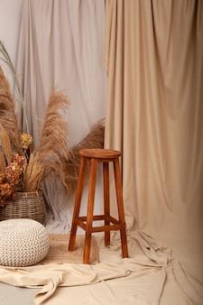 家のсozyインテリア:木製の高いバーの椅子、ニットプーフ、籐のバスケット、ドライフラワーとススキと花瓶。インテリアのドライフラワー。