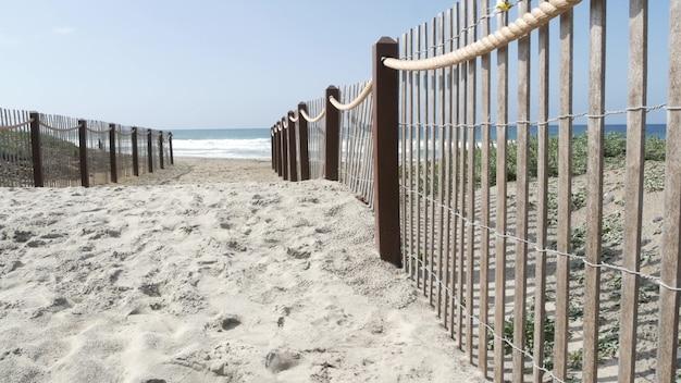 太平洋の海岸、海岸の緑と木製のピケットフェンス。太陽が降り注ぐ夏のビーチ、エンシニータスの海岸線、米国カリフォルニア州の青い水の波。ロサンゼルス近郊の海岸線。沿岸アクセスの入り口。