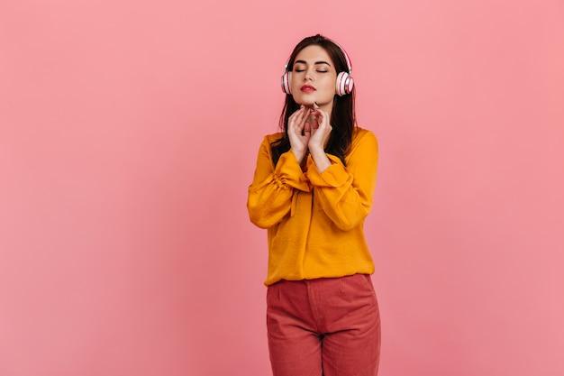 노란색 셔츠와 밝은 바지를 입은 평온한 검은 머리 아가씨는 분홍색 벽에 헤드폰으로 클래식 음악을 즐깁니다.