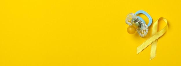 Соска и детская лента осведомленности рака на желтом