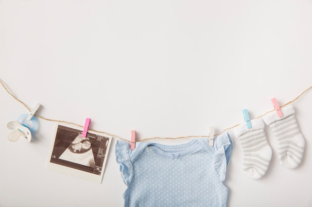Pacifier; sonography picture; socks; baby clothing hanging on clothesline over white background