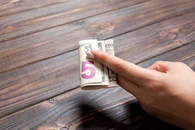 A pack of 5 dollar bills in female hand on wooden table. salary concept with copy space