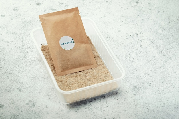 Pack of arugula seeds, plastic container and linen mat.