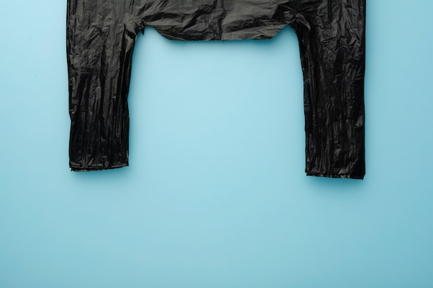Pack black bag on green background. no cellophane. copy space for text.